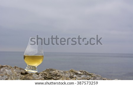 Glass with single malt whiskey standing on a limestone rock with ocean in the background