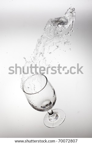 Glass with splash isolated in white - stock photo
