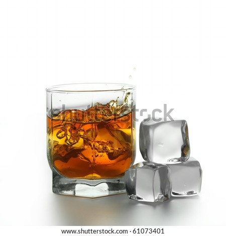 Glass with splashing whisky drink on a white background