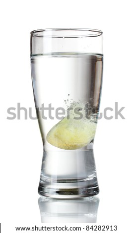 Glass with tablet in water with bubbles isolated on white