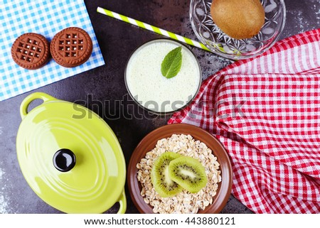 Glass with tasty smoothie breakfast and green paper straw. Tasty sweet diet milkshake with kiwi and mint leaf, rasberries and oatflakes on the black table in the cafeteria or restaurant.  - stock photo