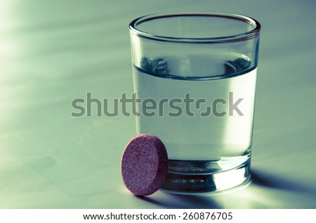 glass with water and pill isolated image - stock photo