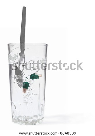Glass with water and pills. - stock photo