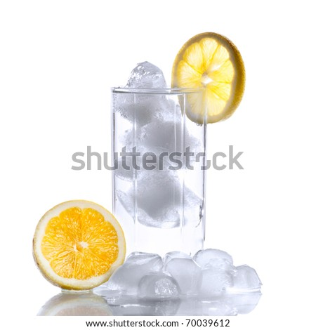 Glass with water, ice cubes and a slice of lemon - stock photo