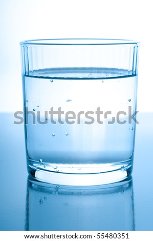 glass with water on glossy background - stock photo