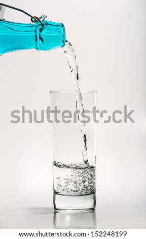 Glass with water pouring from blue bottle