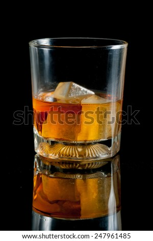 glass with whiskey against a black background