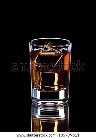 Glass with whiskey and ice cubes on dark background, selective focus, close-up - stock photo