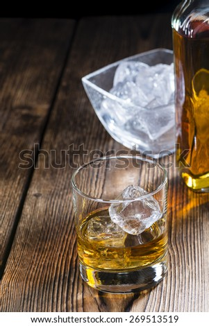 Glass with Whiskey and Ice on wooden background - stock photo