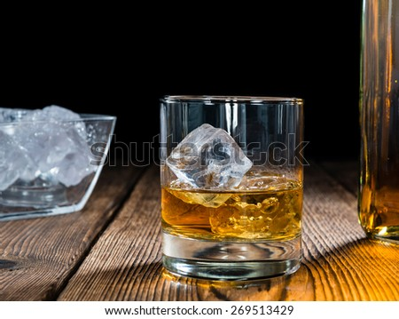 Glass with Whiskey (close-up shot) on rustic wooden background - stock photo