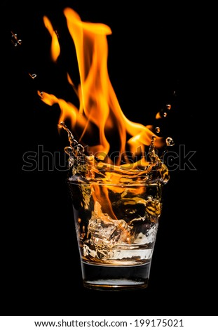 Glass with whiskey splash and fire on black background - stock photo