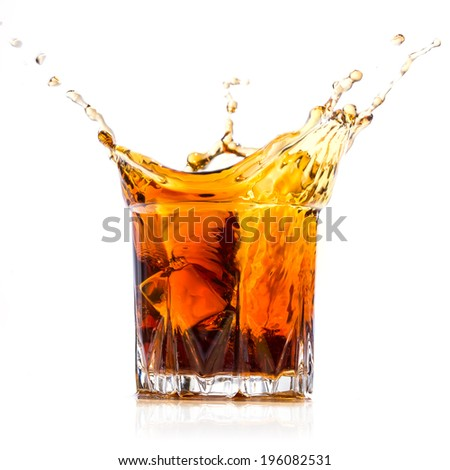 Glass with whiskey splash on white background - stock photo