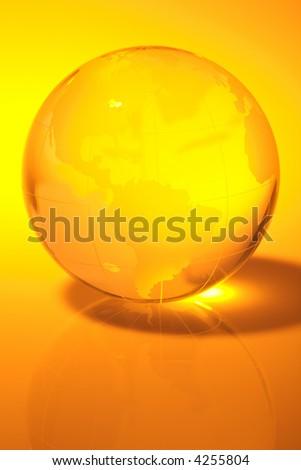 Glass world globe in yellow tone - stock photo