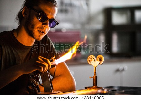 Glassblowing Professional Working on a Torch Flame with Glass Tubes - stock photo
