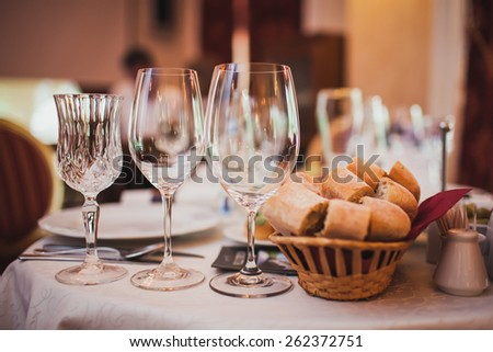 glasses and a basket of bread on the table in a restaurant - stock photo