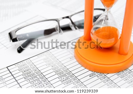Glasses and a sand-glass on documents. - stock photo