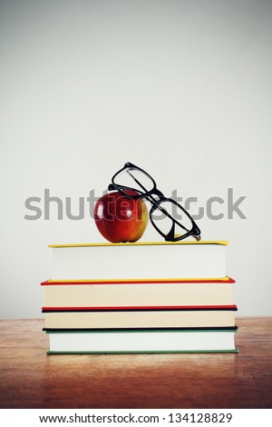 Glasses and apple on a pile of books. - stock photo