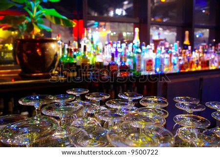 Glasses and assorted colorful bottles of alcoholic drinks in a night-club