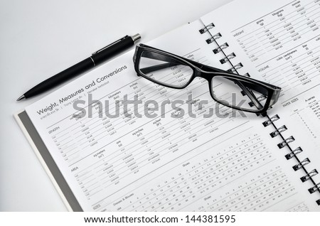 glasses and black pen on weight , measures and conversion book