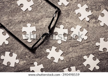 Glasses and blank puzzel pieces. Concept of business challenge, teamwork and solution. - stock photo