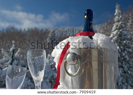 Glasses and bottle of champagne in snow - stock photo