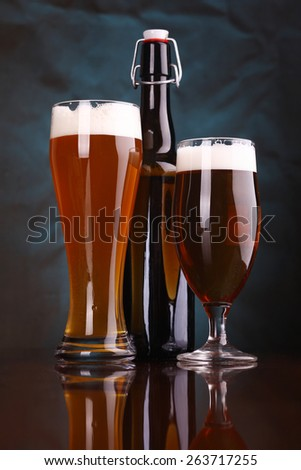 Glasses and bottle of light beer on a wooden table with a blue lit background