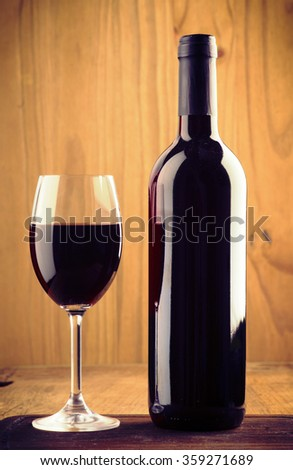 glasses and bottle of wine on old wood