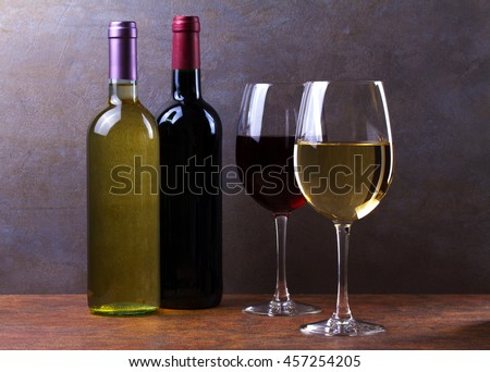 Glasses and bottles of red and white wine - stock photo