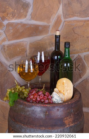 Glasses and bottles of wine, cheese on old  barrel with iron rings - stock photo