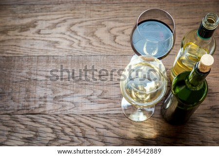 Glasses and bottles with red and white wine - stock photo
