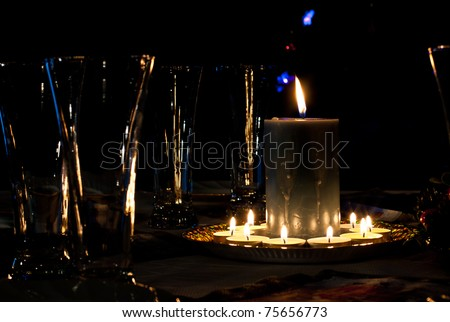 Glasses and burning candles on a table - stock photo