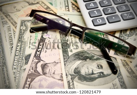 Glasses and calculator on dollars