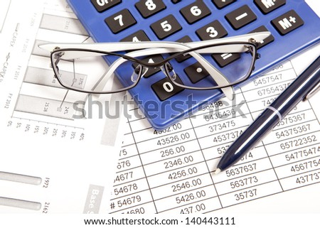 Glasses and calculator on paper table with finance report - stock photo