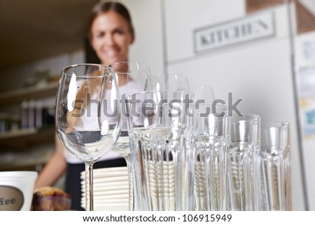 Glasses and dishes from catering service with smiling employee - stock photo