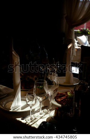 glasses and empty plate on table at luxury wedding reception, catering in restaurant - stock photo