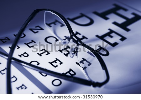 Glasses and eytest chart differential focus blue tone - stock photo
