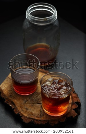 Glasses and jar of filter coffee on a wooden board