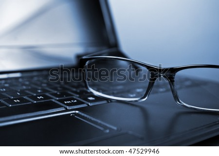 Glasses and laptop in composition blue toned