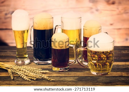 Glasses and mugs with different beers on the wooden table - stock photo