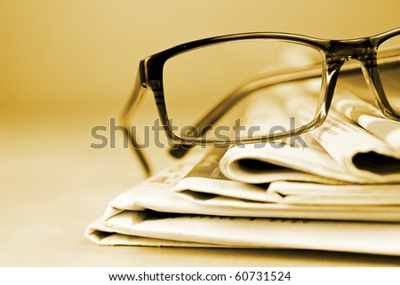Glasses and newspaper in gold tone - stock photo