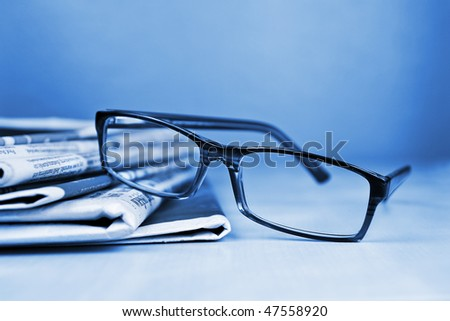 Glasses and newspapers blue toned - stock photo