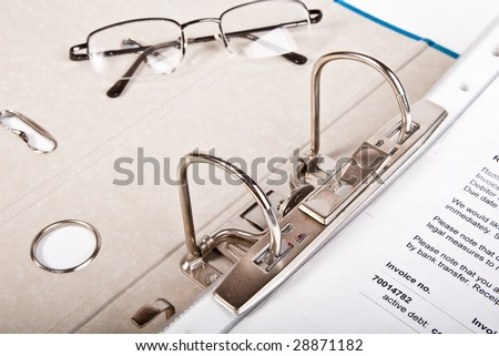 glasses and open binder with invoice - stock photo