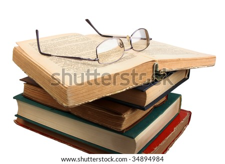 Glasses and open books. Close-up. Isolated on white.