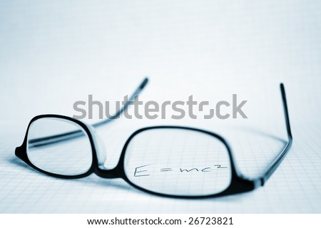Glasses and paper with Albert Einstein's E=mc2 - stock photo