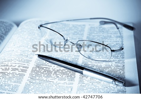glasses and pen laying over an opened book
