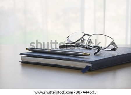 Glasses and pen on a book and table with nature background - stock photo
