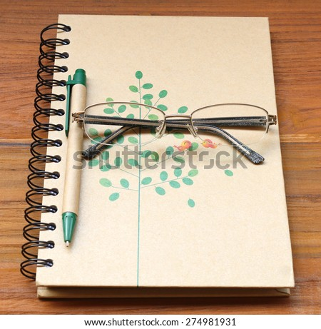 Glasses and pen on a note book - stock photo