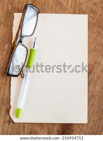 Glasses and pen on old paper on wooden background - stock photo