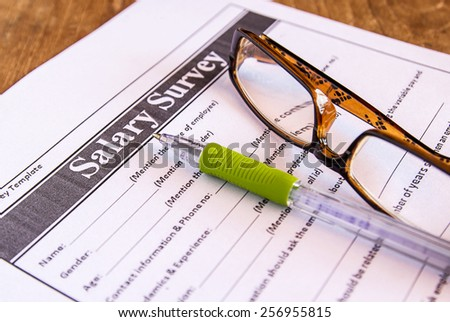Glasses and pen on salary survey from on the table - stock photo
