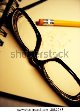 glasses and pencil on book - stock photo